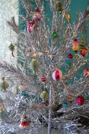 a vintage silver Christmas tree with colorful glass and paper ornaments is classics that will bring vintage charm to the space