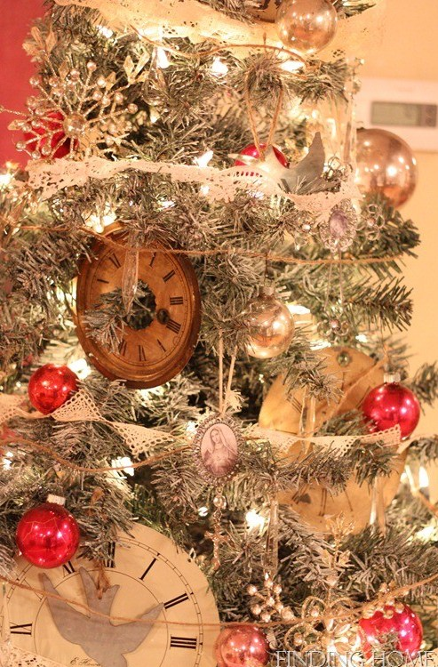 un arbre de Noël avec des lumières, des ornements vintage, des horloges, des flocons de neige et des pommes de pin a l'air très chic et confortable