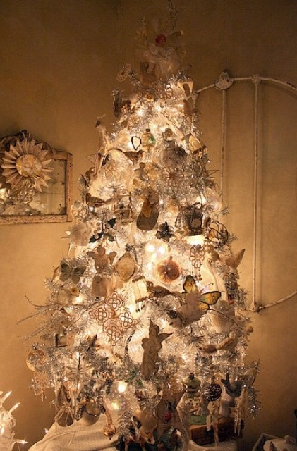 a white Christmas tree with lights and silver and white Christmas ornaments plus snowflakes