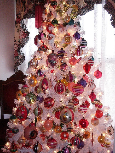 a vintage white Christmas tree with lots of colorful ornaments and lights is a cool idea with plenty of color