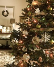 a vintage Christmas tree with green and white ball ornaments, snowflake and silver ones plus lights