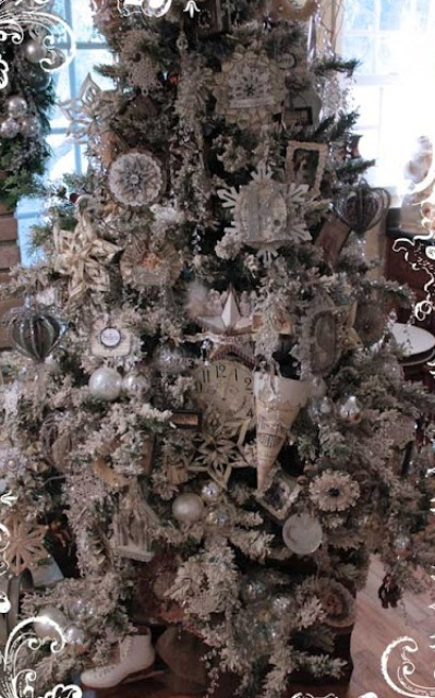 a snowy Christmas tree with white and silver ornaments of glass and paper, with shiny snowflakes and garlands