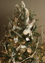 a vintage Christmas tree decorated with white ornaments, paper garlands, lights and ribbons