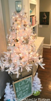 a pure white vintage Christmas tree decorated with lights and kitchen stuff  plus jars with candles for a fun touch