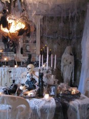a stunning vintage Halloween haunted space with net as spider webs, tall candles, skulls and skeletons, blackbirds and bats is a cool idea for a party