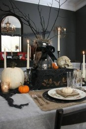a lovely vintage Halloween tablescape with neutral linens, a black table runner, a black chest with a branch arrangement on top, skulls, pumpkins and tall candles