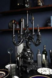 a chic black vintage Halloween candelabra with black candles, vintage glasses and bottles for a beautiful and stylish tablescape