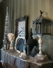 a vintage Halloween mantel with spider webs, skulls, pumpkins, statuettes, a black cage and white pumpkins is a chic and cool idea