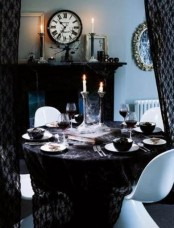 a refined vintage Halloween tablescape with a black tablecloth, white porcelain and black bowls, haunted candleholders with candles is amazing and chic