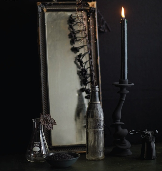 delicate vintage Halloween decor with a mirror, a test tub as a vase, bottle with branches and a black candleholder with a black candle