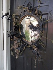 a black mirror with branches, twigs, black leaves and blackbirds is a lovely front door decoration for those who love vintage Halloween decor