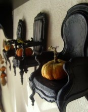 vintage black chairs attached to the walls and with pumpkins on them is a very cute and lovely idea to go for if you love vintage