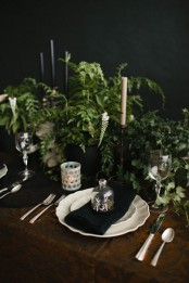 a fresh vintage Halloween tablescape with lots of greenery, black and white candles, white candleholders, porcelain and metallic cutlery is cool