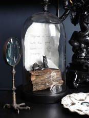 a vintage cloche with wood, a note and some black figurines is always an elegant and cool idea for a vintage Halloween space