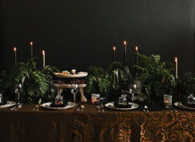 a Halloween tablescape with a rust printed tablecloth, black and white candles, lots of greenery and refined plates and glasses