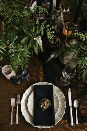 a vintage Halloween table setting with black and white touches, greenery, black candles in vintage candleholders, spiderwebs and hay is a creative idea