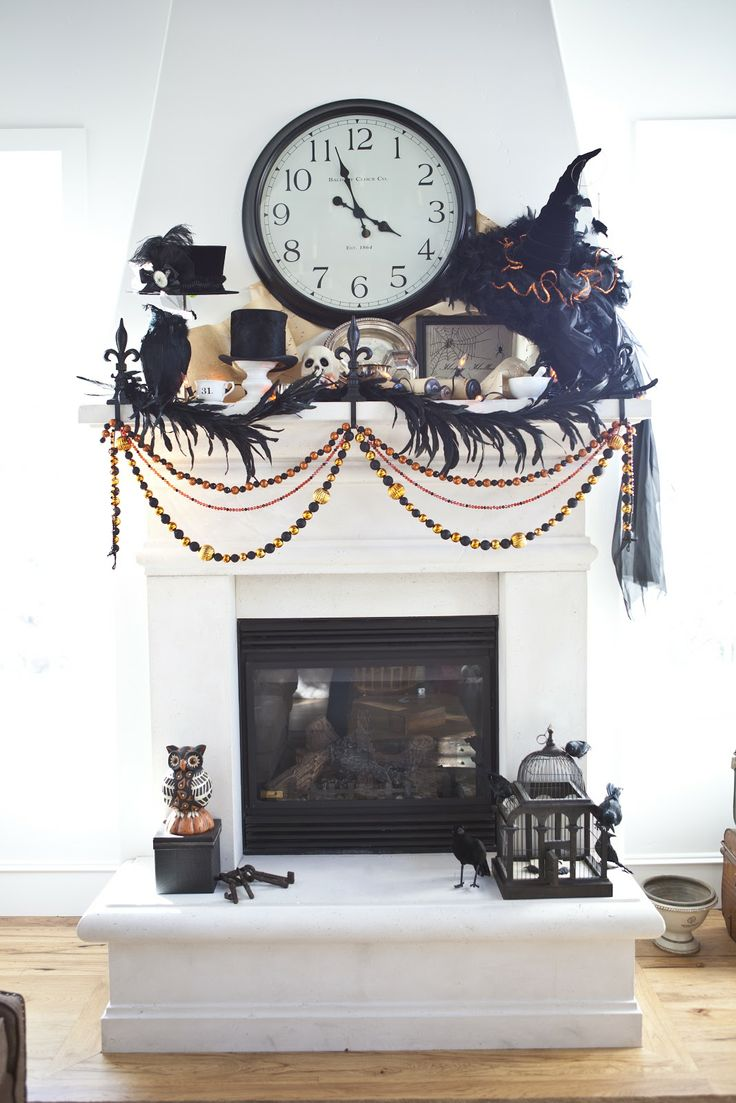 chic vintage Halloween mantel decor with feathers, blackbirds, buntings and garlands, witch hats and skulls is a bold and creative decor idea