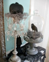 vintage Halloween decor with a tall stand and a cloche, crystals, shiny hay, a black pumpkins and a blackbird is a beautiful idea to DIY