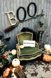 a vintage Halloween nook with a green vintage chair, stacks of vintage books, pumpkins, a broom and some letters