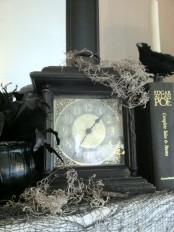 a black vintage clock with moss and a blackbird is a lovely decor idea for a vintage Halloween party