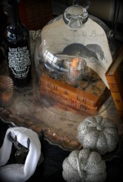 vintage books, a cloche with a candleholder, some ravens and silver pumpkins for lovely vintage Halloween decor
