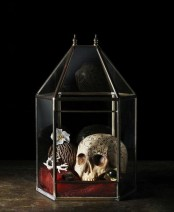 a lovely vintage Halloween decoration of a large candle lantern with a skull, vine balls, blooms and antlers is a cool idea with a refined feel