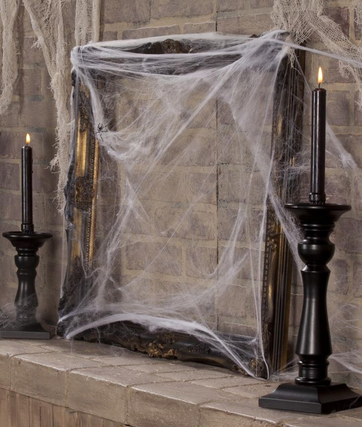 vintage black candleholders with black candles and a vintage empty mirror frame with spider web is a chic and lovely idea for a vintage space