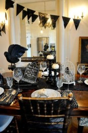 vintage Halloween decor with a black bunting, black linens, blackbirds, white pumpkins and elegant cutlery and glasses