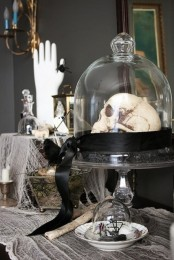 a cloche with a skull on black hay and a black ribbon is a stylish and elegant vintage Halloween decoration to go for