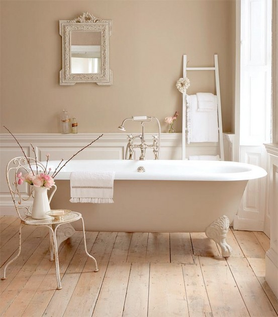 a very relaxing and peaceful taupe and beige bathroom with vintage furniture and a clawfoot bathtub