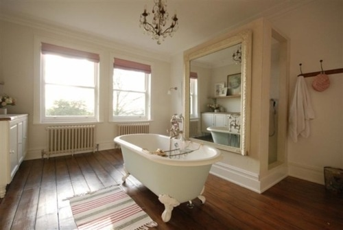a beige and creamy bathroom, a rich colored wooden floor and a large mirror plus windows