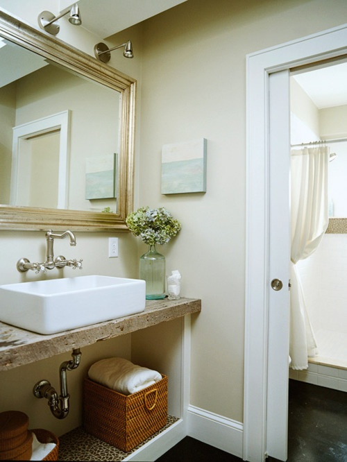 a beige and white bathroom with a rustic vanity surface and a gilded frame mirror