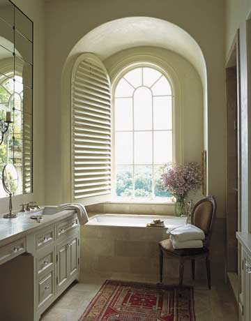 a creamy and beige vintage-inspired bathroom with an arched window and a chic vanity