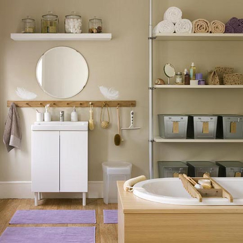 a taupe and light-colored wood bathroom with some white furniture and stainless steel