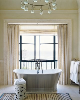 a beige and creamy bathroom with a large window that brigns much natural light inside