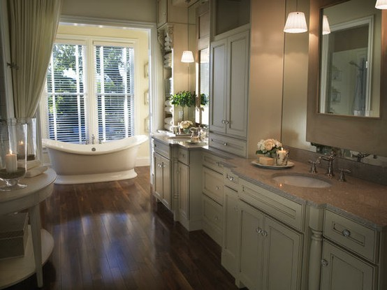 a beige, creamy and brown bathroom with curtains, a dark wooden floor and a large window