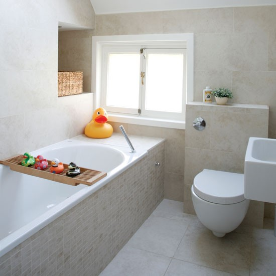 a light beige bathroom clad with tiles, with white appliances and colorful and whimsy accessories