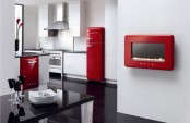 a chic white and red kitchen with red appliances and all white everything, with a black table is a very bright space