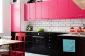 a bold kitchen with lower black cabinets, hot pink upper cabinets, red chairs and a white subway backsplash is cheerful and chic