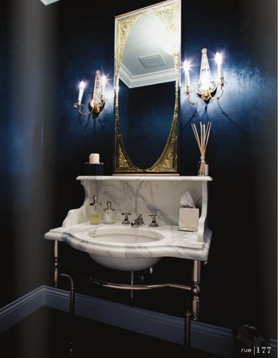 navy walls, a marble vanity and sink plus a mirror in a refined frame for a moody and elegant powder room