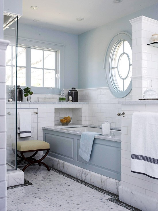 a vintage-inspired light blue and white marble bathroom plus a round window with a frame