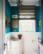 bright blue walls and white paneling are great to make up a cool powder room or bathroom