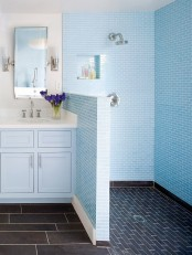 bright blue tiles paired with navy ones in the shower and a light blue vanity