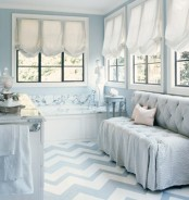 a refined bathroom done with powder blue, with a tufted sofa, a chevron floor and a marble tub
