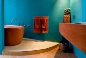 a bright blue bathroom with rust-colored touches and furniture for a bold modern space