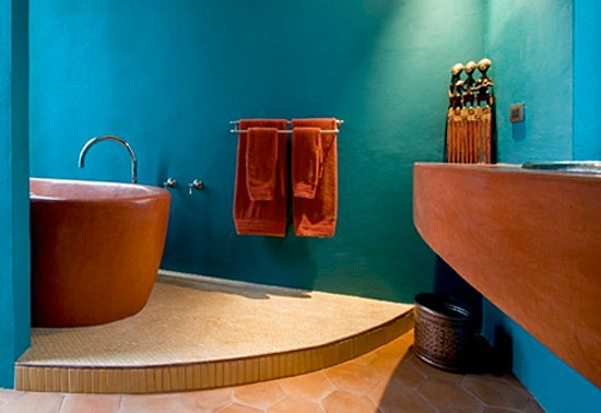 a bright blue bathroom with rust colored touches and furniture for a bold modern space