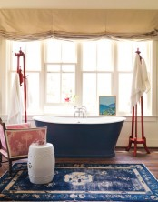 a vintage navy and blue rug plus a navy bathtub to add color and interest to the space