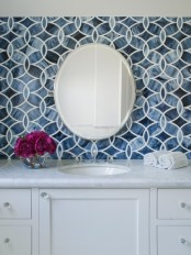navy mosaic tiles, a white vanity and a round mirror for a stylish bathroom sink space