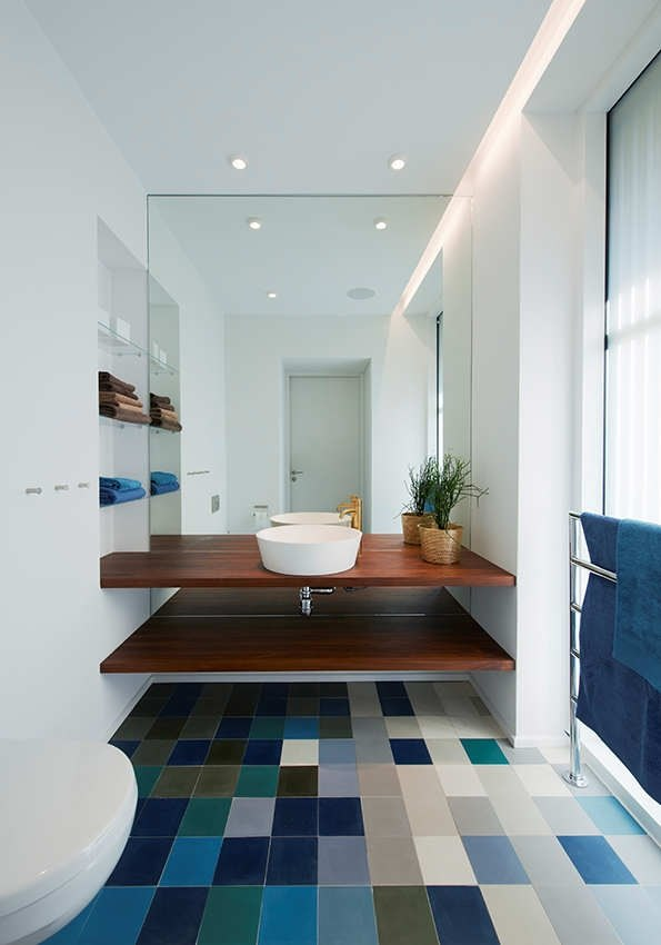 a bright color block tile floor including blues and a matching bold blue towel for a contemporary bathroom