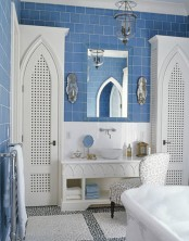 a vintage-inspired bathroom with blue subway tiles and white touches and furniture